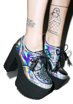 """Current Mood Hologram Creep Queen Platforms cuz so wat if yer a little creeper on da timeline? These sik iridescent platform creepers will keep ya on top of the creep game with a vegan leather construction covered in a reflective hologram and textured rigged 2.5"""" platform and 5"""" chunky heels. Featuring multiple D-rings, contrasting black trim, threaded details at yer toes and flogger lace closure with tassels."""