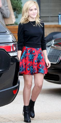 Kiernan Shipka wearing a Celine sweater, Miu Miu floral print skirt, and Acne ankle boots