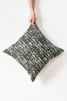 """Lively brush strokes dash across a black background on this boldly patterned pillow cover making it the perfect piece to bring a fun energy to your modern decor. My original """"Raindrop"""" design is printed with eco-friendly ink onto the linen/cotton blend front, and is finished with a natural cotton canvas on the back. Click to buy."""