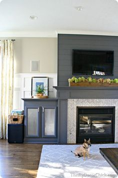 Gray fireplace with marble herringbone tile surround for modern or transitional look...