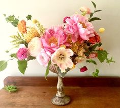 Centerpiece in corals, pink and peach tones with peonies, ranunculus, garden roses, and tulips created by Poppies and Twine Event and Wedding Florist, Yarmouth, Maine
