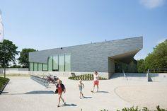 Zwembad als stenen object in groene omgeving - architectenweb.nl
