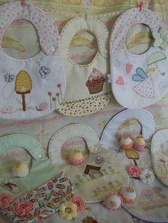 Babetes com aplicação e bordados.
