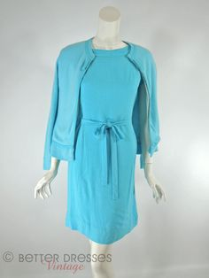 This early 1960s belted shift dress and sweater set in a medium aqua blue is perfect for three seasons. The unlined dress has a banded neckline, princess seams, bust darts, gusseted short kimono-cut s