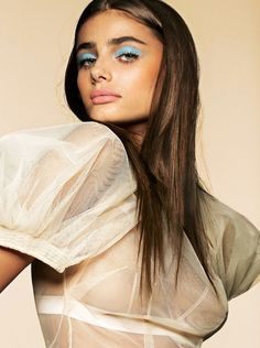 Taylor Hill wears Simone Rocha blouse with blue eyeshadow and pink lip color