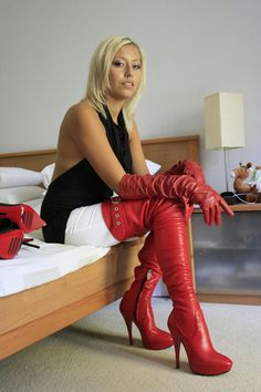 Blonde on bed in red thigh boots and opera gloves