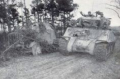 Un M4A3E2 Sherman Jumbo of US 4e Division blindée passe un naufragé allemand SdKfz 7/2 blindée Halftrack transportant un canon antiaérien (éventuellement les 3,7 cm Flak 43). An M4A3E2 Sherman Jumbo of US 4th Armored Division passes a wrecked German SdKfz 7/2 Armoured Halftrack carrying an anti-aircraft gun (possibly the 3.7cm Flak 43).