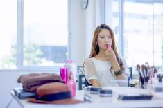 Young woman putting lipstick on her lips stock photo
