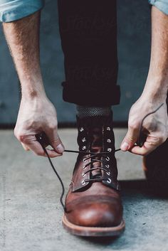 Male tying boot laces outdoors by Treasures & Travels for Stocksy United