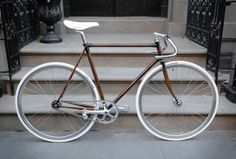 Bicycles: a gorgeous copper fixie bike frame with a white saddle, handlebars and tyres.