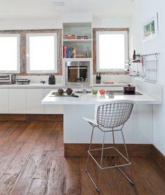 Piso de madeira e tijolinho recortado na parede em um cozinha.