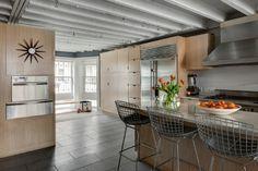 Na cozinha, a marcenaria é no padrão carvalho claro. Destaque para os bancos altos Harry Bertoia e para o relógio de parede Sunburst, desenhado por George Nelson