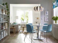 Eetkamer met ronde witte eettafel in combinatie met lichtblauwe stoelen met roestvrijstalen poten