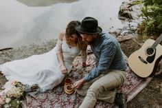 Elopement Picnic By A River With Guitar and Floral Blanket
