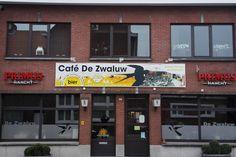 Spandoek opgespannen in klopprofiel aan de gevel van café De Zwaluw in Loenhout.