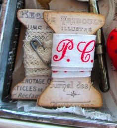 Really like these vintage-print spool embellishments - nice way to incorporate lace - gotta love the tiny pin as well!