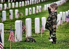 This little man is paying his respects to a loved one at Arlington National Cemetery.