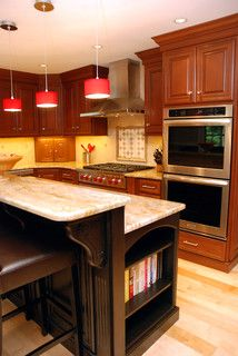 cherry wood kitchen, red pendant lights, ebony wood island with granite countertops and stainless steel appliances, all crafted by local lancaster cabinet makers for this Bryn Mawr, PA Kitchen.    Interior design by down2earth interior design.    www.down2earthdesign.com