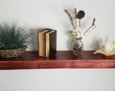 Rustic and elegant. These floating wood shelves are handmade to order and available in various sizes and colors. If you dont see the perfect fit for your home, please send me a message. I am happy to work with you on dimensions and stain color choices as well as answer any questions you may have. The color shown is English Chestnut.  These sturdy shelves slide over a hidden mounting bracket (included). Easy installations instructions are also provided.  Shelves are sold individually…