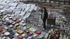 """Artist Song Dong stands amongst his art installation """"Waste Not"""". Article by John Macdonald SMH's art critic"""