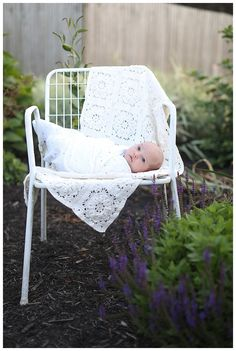 newborn baby girl on white chair/ newborn photography/ baby girl outside in flowers
