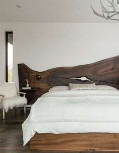 Antler chandelier, rustic wood headboard for the bedroom, mountainous charm with neutral earth tones and a fur over the rocking chair.