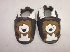 Roar! I am a little lion with my baby shoes in white, brown, and black . First walkers, crib shoes non slip to protect little feet.