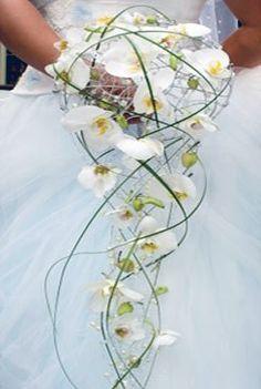 On aime le concept moderne de ce bouquet de mariage cascade avec le côté léger de son armature parsemée d'orchidées blanches