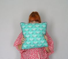 Handmade turquoise bike print cushion, piped and backed in grey and with a concealed zip along the bottom edge.