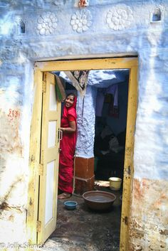 Blue open doorway leads to a smiling Indian woman, Jaisalmer, India. Photography by Jolly Sienda Photography.