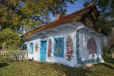 The secluded village of Zalipie in southeastern Poland is home to a charming tradition. Over a century ago the women of the village began to paint their houses. Every house is painted with flowers. Wooden Cottage, Painted Cottage, Painted Houses, White Cottage, Le Blog Du Goumy, Casa Pop, Most Beautiful, Beautiful Places, Glass Building