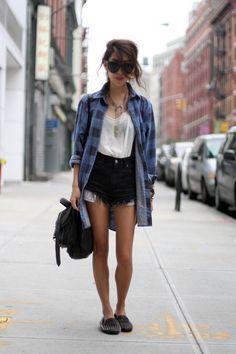 Blue checkered shirt, white tank, black denim shorts, black bag. Casual chic.