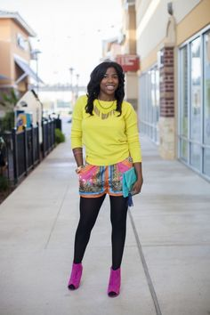 Bright knit/sweater + bold print shorts + black tights + bold booties or pumps