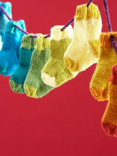 Free Pattern - Add some holiday cheer to your home with these bright and festive #knit mini stockings! #Christmas #holidays