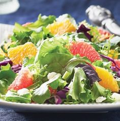 Mixed greens with orange segments and crumbled cheese