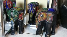Lowering its trunk toward the ground, a majestic elephant is hand-carved of sese wood and recycled glass beads. This royal sculpture is from Ghana