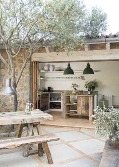 I love this outdoor area shaded by olive trees Small, rustic kitchen tucked behind folding glass doors in this stone home in Spain