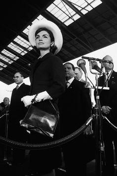 Damenhaft mit Hut und weißen Handschuhen empfängt Jackie Kennedy 1963 den Shah von Persien.