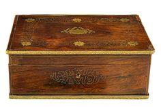 CAJA JOYERO CARLOS X. C. 1830 Madera de palosanto con rebordes en latón con dibujos geométricos y vegetales. Adornos mixtilíneos y flores en latón en tapa. Interior con espejo y raso rojo.Medidas: 12 x 33 x 23 cm.
