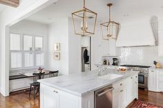 A pair of antique brass Darlana  Lanterns hang over a white kitchen island topped with marble fitted with a sink and deck mount faucets lined with backless bistro stools, Serena & Lily Riviera Backless Stools atop a stained oak wood floor.