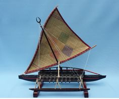 """Side view of the Fiji canoe Camakau , also called Thamakau with its beautiful matted sail and masthead, the """"domodomo"""