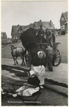 Boetsters op de Dr. Lelykade aan het werk, staand mevrouw Vooijs - Hoogendijk (moeder van Cor Vooys, vuurtorenwachter) zittend Jannetje Verheij - Vink (geb. 05-08-1899, ovl. 27-12-1982); een nettenwagen wordt geladen met de gerepareerde netten; op de achtergrond de Schokkerweg. ca 1955 Rembrandt, Amsterdam, nr. 88 #ZuidHolland #Scheveningen