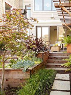aménagement jardin en pente avec allée en pierre, murs de soutènement en bois clair et terrasse moderne