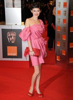 Audrey Tautou in a pink dress with red high heels and clutch bag
