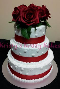 3 tier wedding cake iced in butter cream with polka dots. wrapped with red ribbon and red roses for topper.