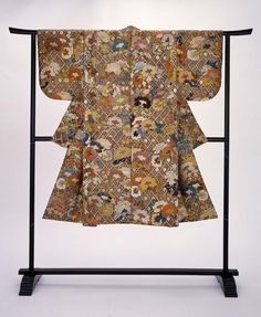 Dark brown silk Noh theater robe with overall design of peonies on cypress fence in green, blue, light brown, purple, orange, white, pink and gold supplemental weft patterning with some later embroidery. There is a reddish-orange plain-weave silklining.