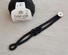Handmade french knitted black cotton bracelet with one pearl button.    The circumference is 21cm.    Each item is package in a small white fabric bag, making it a stylish gift as well as a special treat for yourself !    I send all over the world by priority delivrery, the cheapest one with no tracking. If you prefer another type, please contact me before.    Thank you