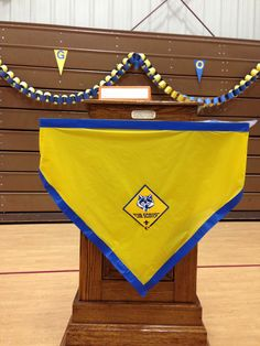 Blue & Gold Banquet decoration. DIY. Leftover piece of yellow plastic table cloth, blue painters tape & cutout emblem from the table topper package.