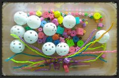 Fine Motor Sensory Bin focused on the motor planning needed to string beads. The bin includes practice golf balls, pony beads, foam beads, skinny pipe cleaners, and skinny silly straws.