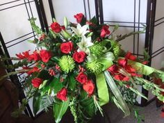 Peaceful Passage-casket spray, red roses, bells, red glads, red hypericum, green fuji & lilies, leather, aspidistra ,aralia and ivy